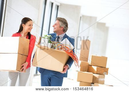 Smiling businessman and businesswoman looking at each other while carrying cardboard boxes in new office