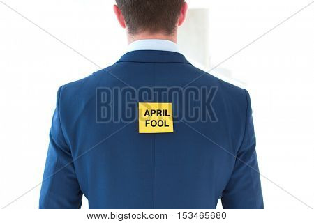Rear view of young businessman with april fool sticky note at office