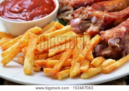Fried potatoes pork ribs and tomato sauce close up view