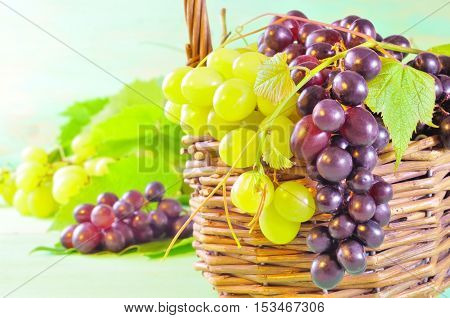 Red And Green Grape Bunches And Leaves In Basket On Wooden Table