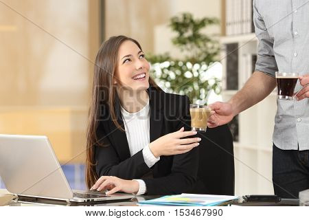 Businessman giving coffee to his colleague who is working with a laptop at office