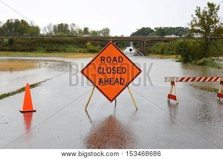 Road Closed Ahead Sign Over Rain Flooded Street