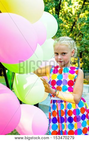 girl stands near the balloons outdoors in summer
