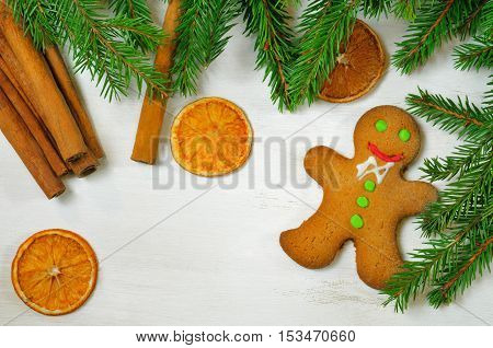 Gingerbread mans and Christmas tree branches on wooden background