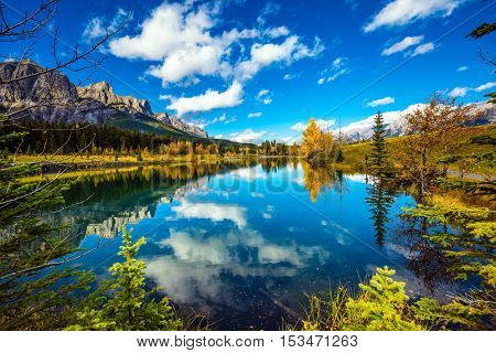 Concept hiking. Bright shining day in the Canadian Rockies. Canmore, near Banff. Jagged mountains and red-orange trees are reflected in smooth water of the lake
