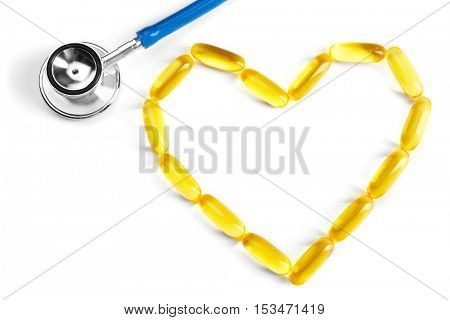 Cod liver oil capsules in heart shape with stethoscope on white background
