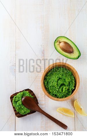 Traditional mexican sauce guacamole in bamboo bowl lemon and cut half avocado on white wooden background. Selective focus. Text place.
