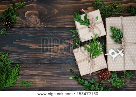 Christmas background with hand crafted gifts presents on rustic wooden table. Christmas or New year DIY packing. Holiday decor concept. Overhead flat lay top view copy space