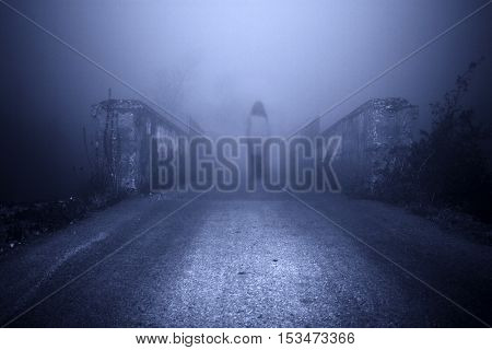 Mystical woman in white standing in the middle of the road