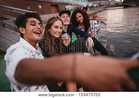 Shot of young man taking selfie with friends sitting on jetty on the lake. Teenagers having fun outdoors taking self portrait with mobile phone.