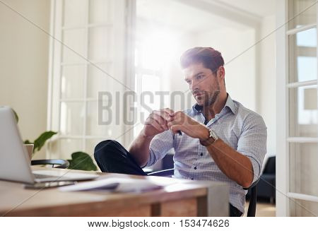 Shot of young man sitting at table looking at laptop and thinking. Thoughtful businessman working at home office.