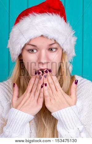Christmas time. Young woman wearing santa claus hat red dress on blue background. Surprised face expression.
