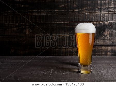 Glass of beer with frost on wooden background