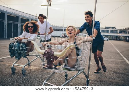 Young people racing with shopping trolleys on road. Multiracial group of friends racing with shopping cart.