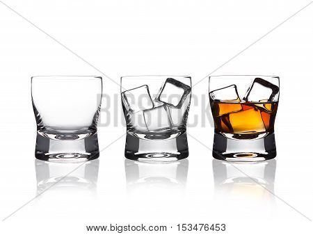 Glasss of whiskey with ice cubes with reflection on white background
