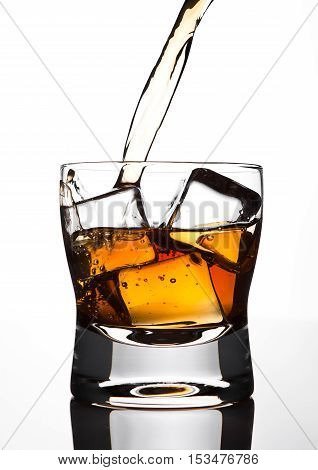 Pouring whiskey to the glass with ice cubes on white background
