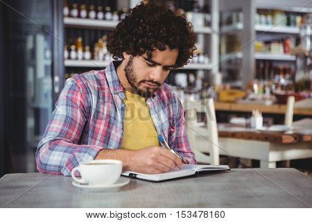 Man writing on a diary in cafeteria