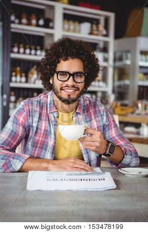 Portrait of man smiling while having coffee in cafeteria