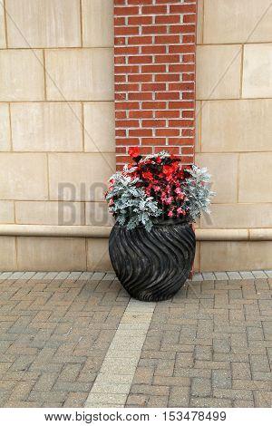 Beautiful gray pot holding plants and seasonal flowers set on brick walkway.