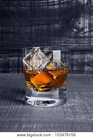 Glasss of whiskey with ice cubes on blue wooden background