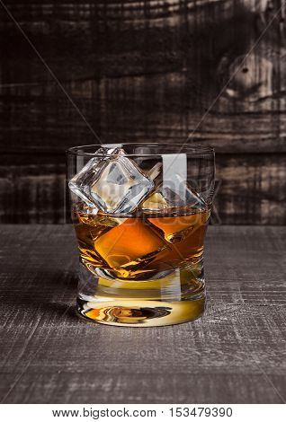 Glasss of whiskey with ice cubes on wooden background