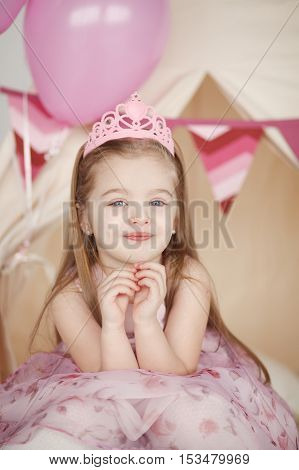 Vertical portrait of cute smiling little girl in pink princess dress celebrating her birthday