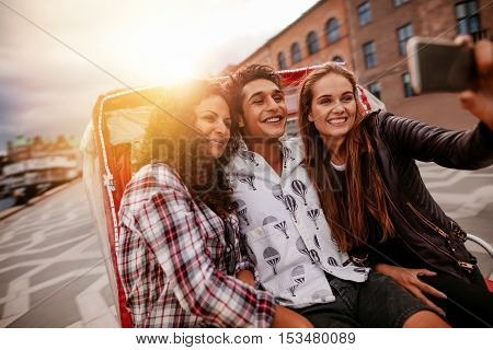 Teenage friends having fun on vacation traveling on tricycle and taking selfie with mobile phone. Young man and women riding on tricycle bike and taking selfie.