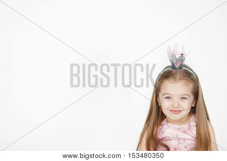Portrait of cute little girl wearing princess pink dress and crown with copy space for text on white background.