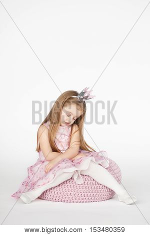 Beautiful girl looking sad and tired. Vertical portrait of cute kid with blond long hair isolated on white background