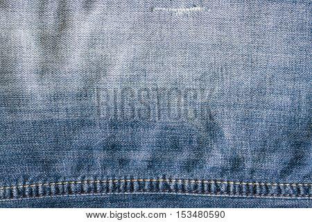 Blue vintage denim jeans texture with thread. Jeans background crumple.