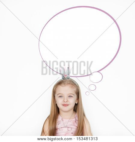 smiling little girl against white background with a speech bubble above head. Cute princess girl dreaming thoughts