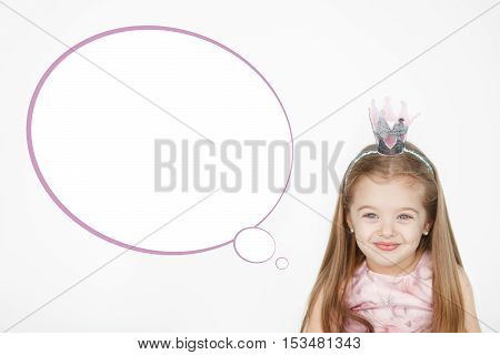Portrait of cute little girl wearing princess pink dress  and crown with speech bubble and copy space for text on white background.