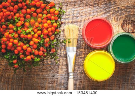 cans of paint with brush wooden background top view close up