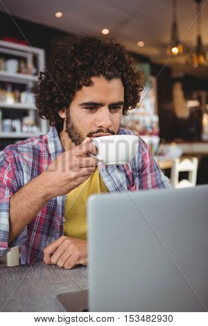 Man having coffee while looking at laptop in cafeteria