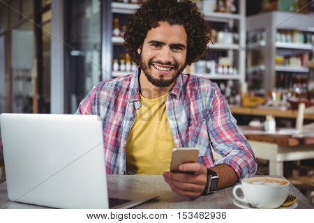 Portrait of happy man holding mobile phone in cafeteria