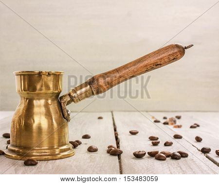 A photo of a vintage coffee pot with a wooden handle, side view on a light wooden background texture with copyspace, with coffee beans scattered around, slightly toned
