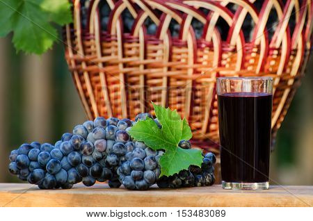 Large bunch of ripe grapes and a glass of juice on a background of a wicker basket