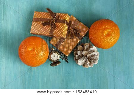 A photo of two gift boxes, tangerines, a pine cone, and a vintage chain clock showing midnight. A New Year or Christmas greeting card on a blue background with copyspace.