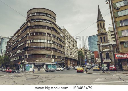 Bucharest Romania - April 22 2014: View of the corner of Stirbei Voda and Luterana streets intersection with interwar building on the left side and the Lutheran Church on the right side.