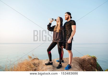 Full length of a young sports man and woman resting after jogging outdoors