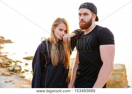 Beautiful young sports couple resting after workout while standing at the beach