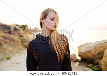 Portrait of a beautiful young sports girl standing outdoors at the beach
