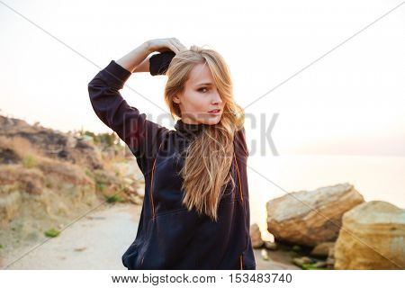 Portrait of a young woman doing stretching exercises outdoors in the morning