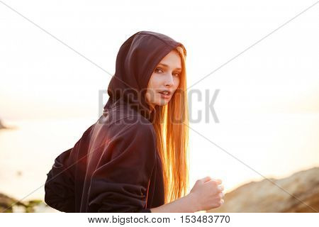 Young woman athlete running in the morning along seashore and looking at camera