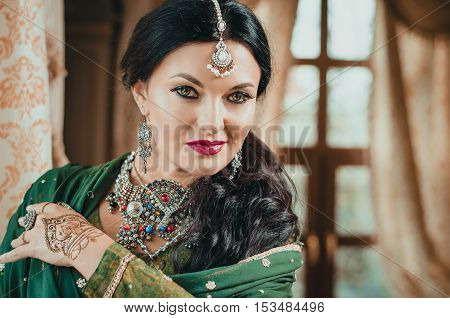 portrait of a beautiful woman in Indian traditional Chinese dress with her hands painted with henna mehendi.
