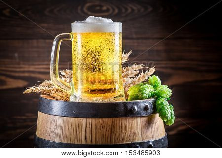 Cold And Fresh Beer In Glass On Wooden Barrel