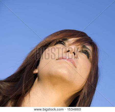 Attracive Young Woman Looking Out Towards The Clear Blue Sky.