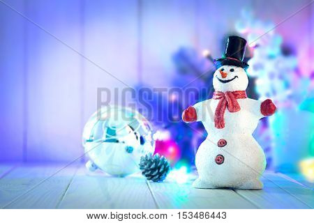 Christmas snowman with balls and garland on wooden board copyspace