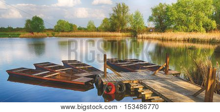 Summer season landscape. Pier and five wooden boats. The place is one of the backwaters of the Tisza river in Tiszalok, Hungary. Sunset. Warm dry calm weather.