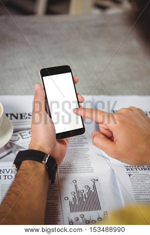 Hands of man holding mobile phone in cafeteria